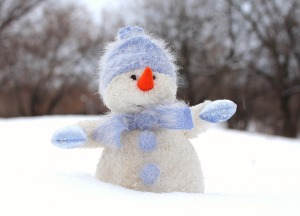 Snowman with light blue gloves, cap and scarf, and big orange nose