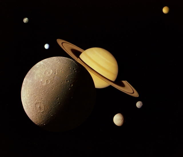 This montage of images of the Saturnian system was prepared from an assemblage of images taken by the Voyager 1 spacecraft during its Saturn encounter in November 1980. This artist's view shows Dione in the forefront, Saturn rising behind, Tethys and Mimas fading in the distance to the right, Enceladus and Rhea off Saturn's rings to the left, and Titan in its distant orbit at the top. https://en.wikipedia.org/wiki/Saturn