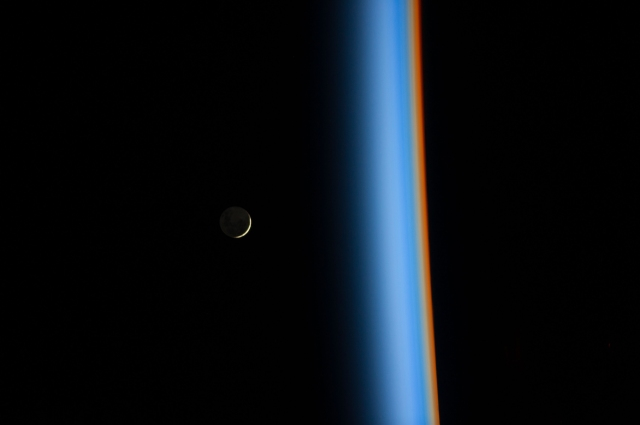 NASA image of the moon taken on Feb. 1, 2014 by Japan Aerospace Exploration Agency astronaut Koichi Wakata, who tweeted this view of a crescent moon rising and the cusp of Earth's atmosphere. Distinct colors are visible because the dominant gases and particles in each layer of the atmosphere act as prisms, filtering out certain colors of light. https://www.nasa.gov/content/crescent-moon-rising-and-earths-atmosphere