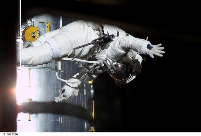 NASA Astronaut Richard Linnehan waves to crewmates inside the space shuttle Columbia during a space walk to work on the Hubble Space Telescope, March 4, 2002, S109E5236 image from https://images.nasa.gov/details-S109E5236.html
