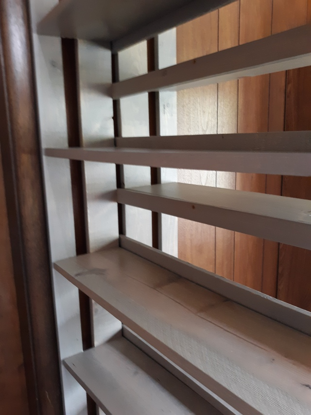 Angle view of Debey's double-sided bookcase showing how the shelves align with the back supports on the opposite side.